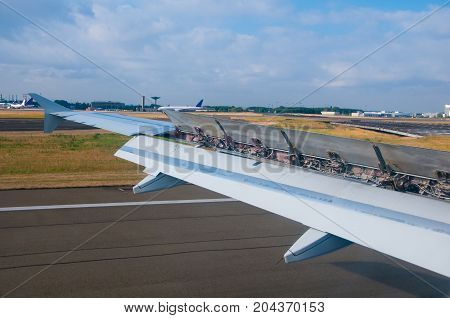Plane is landing on runway in airport on along landing strip. Flaps are released on the plane wing to top it efficiently