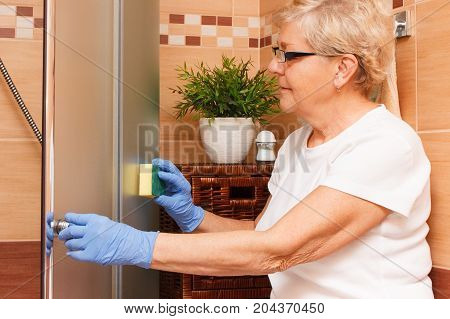Senior Woman Wiping Shower Cabin Using Sponge, House Cleaning And Household Duties Concept