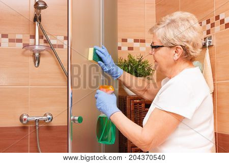 Elderly Senior Woman Cleaning Shower Using Sponge And Detergent, Household Duties Concept