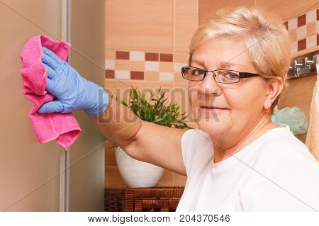 Senior Woman Wiping Shower Cabin Using Pink Microfiber Cloth, House Cleaning And Household Duties Co