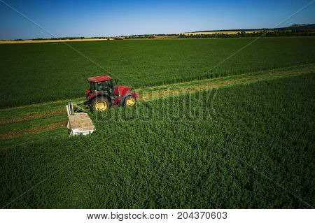 Acricultural Tractor mowing green field aerial view