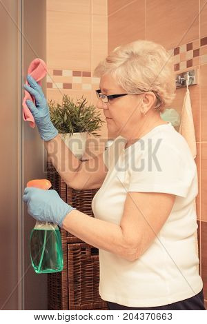 Senior Woman Using Pink Microfiber Cloth, Detergent And Cleaning Shower, Household Duties Concept