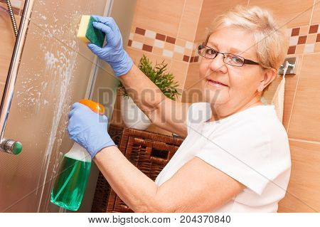 Elderly Senior Woman Using Sponge And Detergent For Cleaning Shower Door In Bathroom, Concept Of Hou