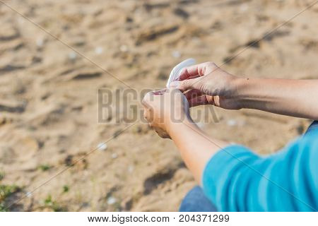 Woman holds a white feather of a seagull in hand. Symbol of lightness and fragility.
