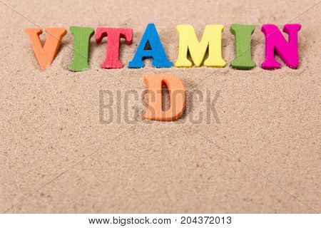 Word vitamin D of colored wooden letters on sandy beach