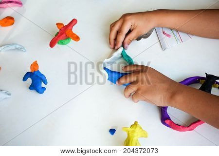 children learn and fun with modeling clay on white table