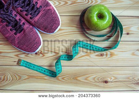 Sneakers, Centimeter And Fresh Apple Top View. Healthy And Active Lifestyles. Wooden Background.