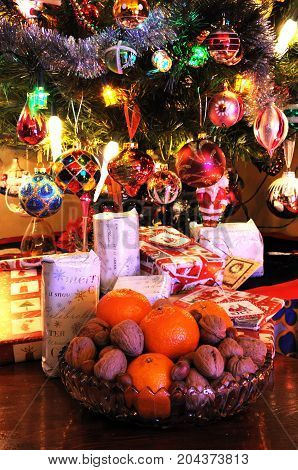 Glass bowl filled with walnuts hazelnuts and mandarin oranges with Christmas presents under tree to the rear England UK Western Europe.