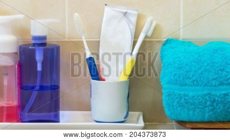 Toothbrushes with Bathroom set dispenser and soap on stool in a bathroom closeup.