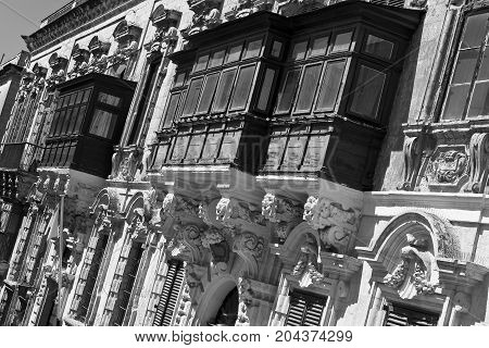 Typical narrow street on the island of Malta. Buildings with traditional colorful maltese balconies in historical part of Valletta. Black and white picture