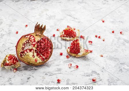 Half of the ripe pink pomegranate on a light marble background with scattered grains on the background. Procurement for design. Top View