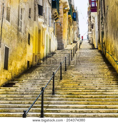Typical narrow street with stairs on the island of Malta. Buildings with traditional colorful maltese balconies in historical part of Valletta.