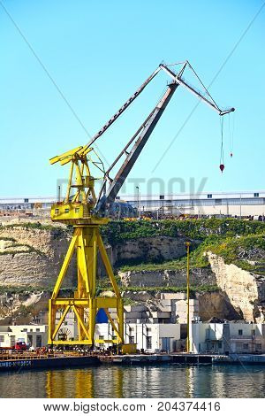 PAOLA, MALTA - MARCH 31, 2017 - Industrial cranes in the docks with buildings to the rear Paola Malta Europe, March 31, 2017.