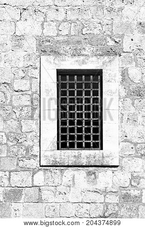 Barred window of traditional stoned house in old Acre. Window in the old city of Akko in Israel. Black and white picture