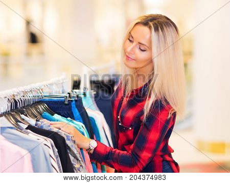 Young blonde smiling attractive woman with long hair shopping in the fashion wear garments apparel store and choosing the clothes