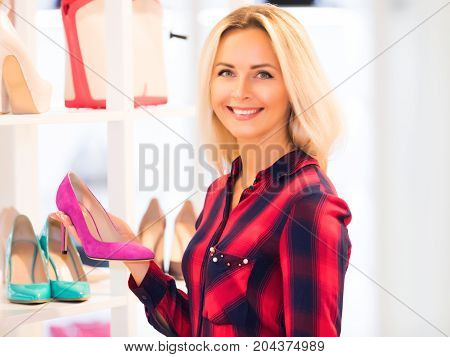 Young blonde smiling attractive woman with long hair shopping in the fashion footwear store and holding a pink high heels shoe in the hand