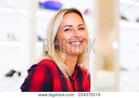 Head and shoulders portrait of young attractive smiling woman with long blonde hair in the fashion wear garments apparel store