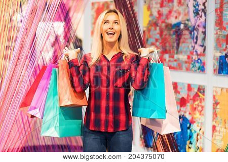 Young happy attractive woman with a lot of color shopping bags in the modern fashion store