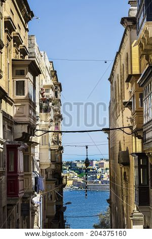 Typical narrow street leading to the sea on the island of Malta. Buildings with traditional colorful maltese balconies in historical part of Valletta.