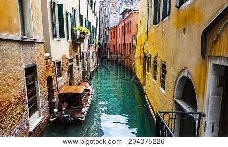 Houses peeling off from dampness. Venice is situated across a group of islands that are separated by canals and linked by bridges. Gondola is a traditional flat-bottomed Venetian rowing boat