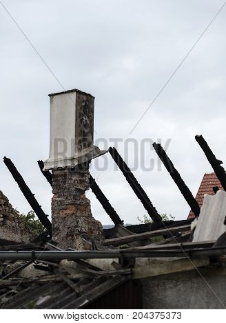 Burnt house roof with a chimney and beams.