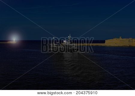 Cargo ship leaves the harbor of Valletta at night. Lighthouses indicate the entrance to the ports of Malta