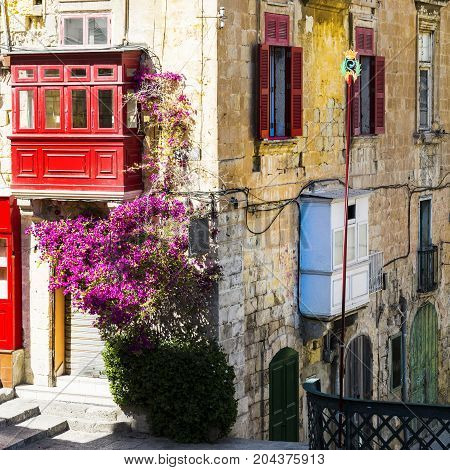 Building with traditional colorful maltese balcony in historical part of Valletta. Red windows decoreted with begonville on the facade of a house in Malta
