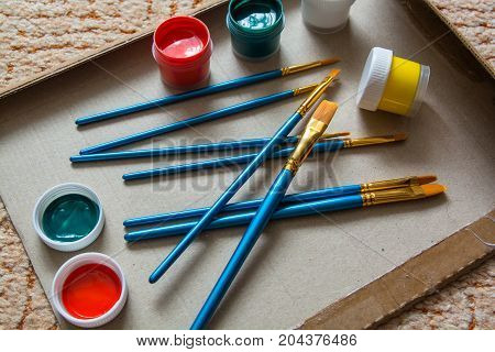 Heap of art brushes and few jars of paint. Artist work place.