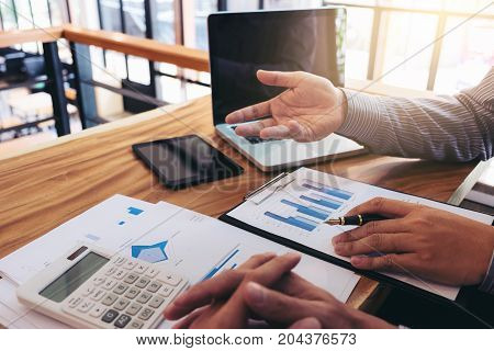 Co working conference Business team meeting present investor colleagues discussing new plan financial graph data on office table with laptop and calculator Finance accounting investment.