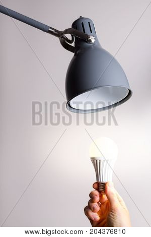 Changing the bulb for led bulb in floor lamp in gray colour.