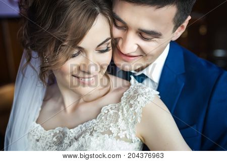 close up portrait of newlywed couple hugging. Bride in beautiful wedding white dress and asian groom in dark blue suit. Hugging and smiling
