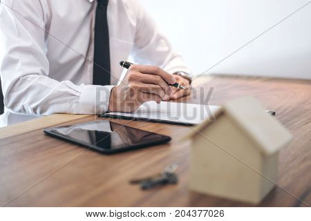 Man sign a home insurance policy on home loans Businessman signing contract insurance.
