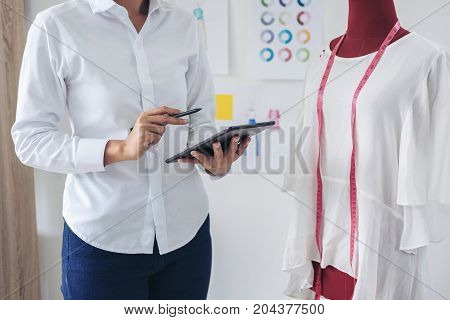 Stylish fashion designer working with measure red dummy as sketches in digital tablet of new collection in art profession and job occupation Creative Design and Artistic Concept.