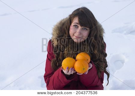 white woman sit and hold orange fruits winter outdoors