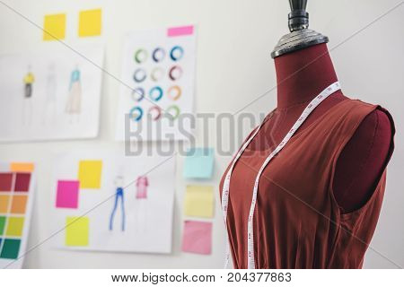 Red dummy with measuring tape in tailors studio Creative Design and Artistic Concept.