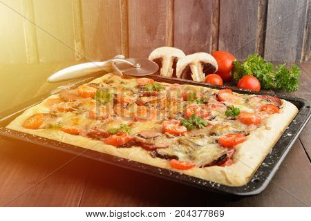 Pizza at home with some ingredients and special knife over wooden background with copy space toned photo