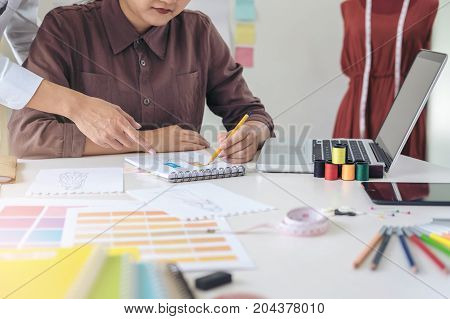 Two professional stylish fashion designer working as fashion designers measure as sketches in workshop of new collection in art Creative Design and Artistic Concept.