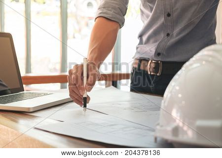 Image of engineer or architectural project Close up of engineer's hand drawing plan on BluePrint with Engineering tools on workplace.