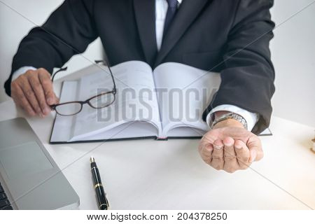 Image of Male lawyer or judge importune bribes client working with Law book report the case on table in modern office Law and justice concept.