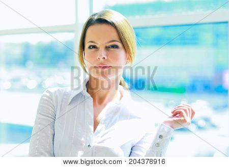 Young woman standing near wall in office.