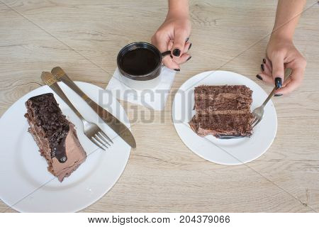 Female hands holding cup of coffee and cookies on wooden table. Girl eating a piece of cake and cup coffee