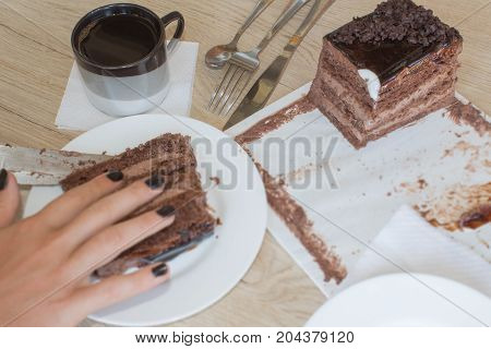 Eat chocolate cake with coffee in a relaxing time. Female cutting chocolate cake on wooden table.
