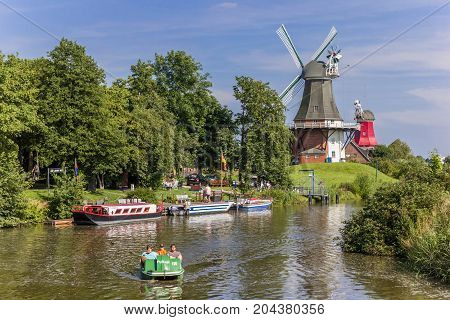 GREETSIEL, GERMANY - JULY 18, 2017: Tourists in a paddle boat on the river in Greetsiel, Germany