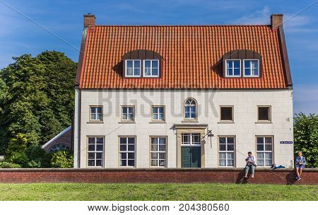 GREETSIEL, GERMANY - JULY 18, 2017: Old house and tourists in the historic center of Greetsiel, Germany