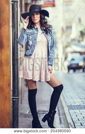 Young Brunette Woman Standing In Urban Background.