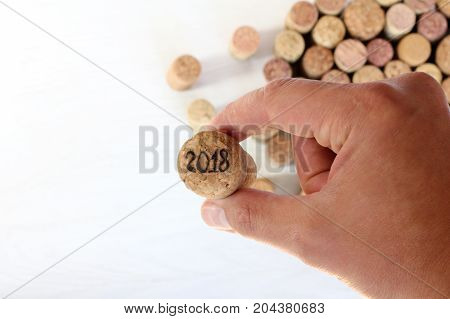 hand holds a large cork from the sparkling wine with the number / new year 2018