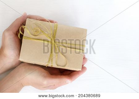 festive gift in hands top view / presenting a surprise in box