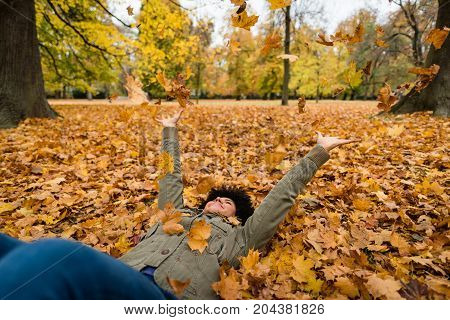 Woman lying on dry maple leaves during fall season