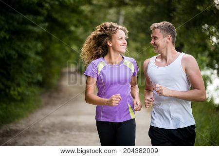 Happy couple runners jogging down the gravel trail