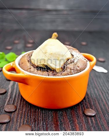 Cake with chocolate and pear in red roaster and mint on a wooden boards background